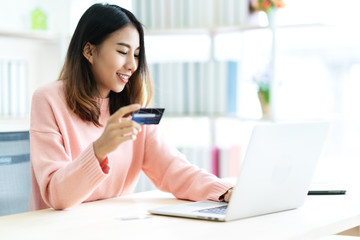 Young attractive asian woman holding credit card sitting at table typing keyboard on laptop computer to shopping online at home office or library. Happy girl student buy and pay in ecommerce concept.