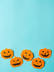 Halloween concept. Paper origami pumpkin on bright blue background. Simple idea for halloween - easy made paper pumpkins on light blue color background. Copy space for text. Banner. Vertical