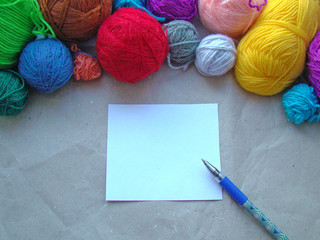 A sheet of paper, a pen and a knitting yarn