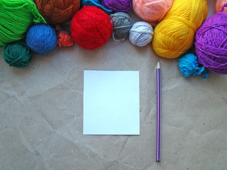 A sheet of paper, a pencil and a knitting yarn