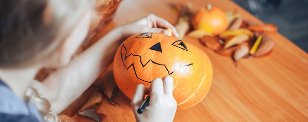 Preparation for Halloween: woman hands paint orange pumpkin with black paint. Closup. Holiday decoration concept.