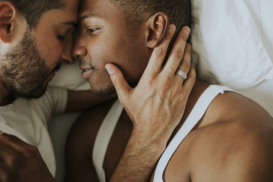 Gay couple cuddling in bed