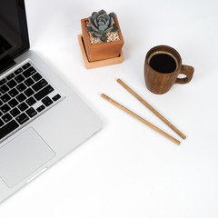 Home office workspace mockup with notebook, cactus, coffee cup on white background, Flat lay, top view