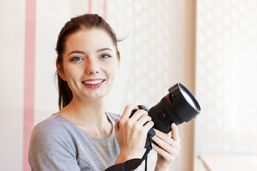 Portrait of Girl photographer smiling and holding her camera