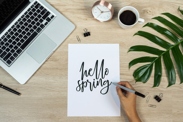 Home office workspace with laptop, palm leaf, notebook and card with quote Hello Spring written in calligraphic style on paper on wooden background. Flat lay. top view.