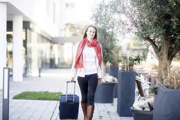 Frau mit Reisekoffer aussen