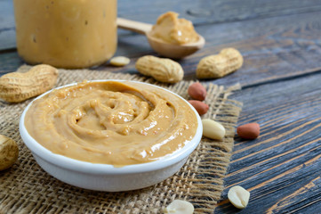 Peanut butter in a ceramic bowl on a wooden table. A traditional product of American cuisine.
