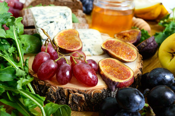 Assortment of appetizer: grapes, cheese, blue cheese, figs, melon, arugula, grain bread, honey on a round wooden tray on a wooden table
