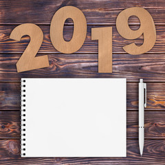 Cardstock Numbers 2019 Happy New Year Sign near White Spiral Paper Cover Notebook with Pen over table. 3d Rendering