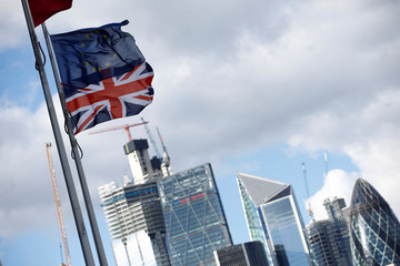 Flags flutter in the wind with the financial district in the background, in London