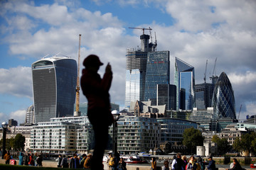 A person takes a photograph with the financial district in the background, in London