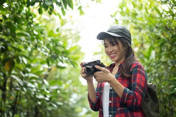 Asian girl traveler in red plaid shirt holding retro camera.