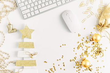 Christmas home office desk with computer, christmas tree, gift, golden decorations. Flat lay, top view, copy space