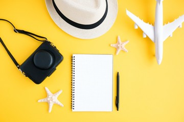 Traveler accessories. Photo camera, hat, airplane, notebook, seashells on a yellow background.Travel vacation concept. Summer background.