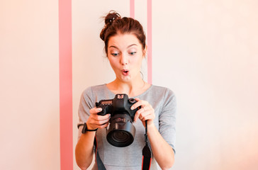 Pretty girl photographer looks into her camera and makes funny s