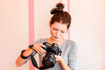 Pretty girl photographer looks into her camera and makes funny d