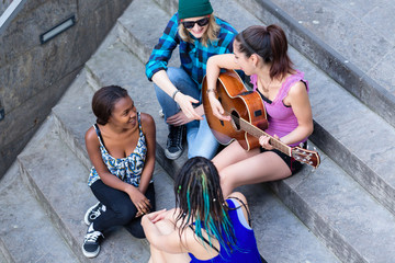 Overhead view of woman playing guitar with her friends sitting on staircase