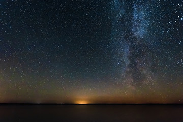 Blue Night Starry Sky With Milky Way Galaxy Above Lake And Russian Village. Night Glowing Stars