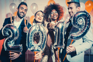 Party people women and men celebrating new years eve 2019 with sparklers and Champagne