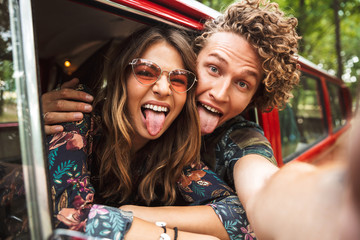 Photo of traveling hippie couple smiling, and showing peace sign while driving retro minivan in forest