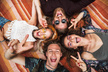 Portrait of lovely hippies friends guys and girls laughing, and lying on blanket in circle outdoor
