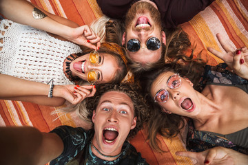 Portrait of happy hippies people laughing, and lying on blanket in circle outdoor