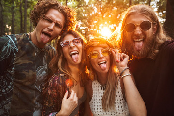 Photo of four hippie people men and women, smiling and taking selfie in forest