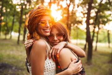 Photo of two caucasian hippie girls, smiling and hugging each other while walking in forest