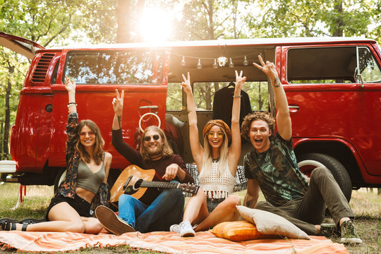 Group of friends hippies men and women laughing, and sitting near vintage minivan into the nature