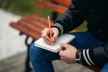 Student in a black jacket sits in a park on a bench writes down his thoughts in a notebook. Handsome boy