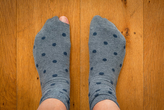 A pair of socks. A sock with a hole. the big toe shows through a hole in the sock.
