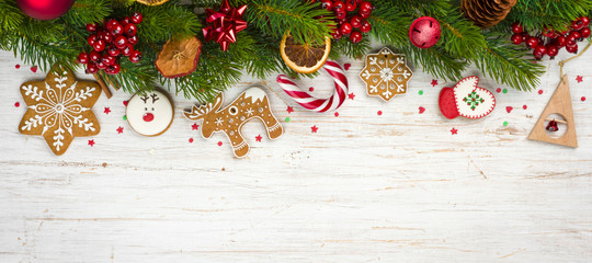 Christmas background concept, decorated holiday tree branches and gingerbread cookies