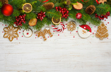 Christmas background with tree branches, ball toys, stars, gingerbread cookies