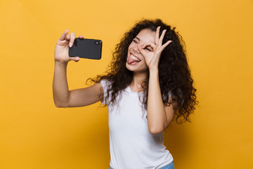 Happy cute young woman posing isolated over yellow background take a selfie by mobile phone.