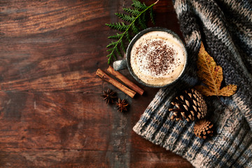Cup of cappuccino coffee with spices for a cold autumn day. Flat lay. Wooden background. Copy space