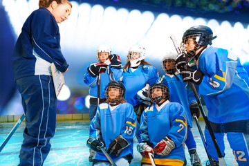 Female coach and hockey team discussing game plan
