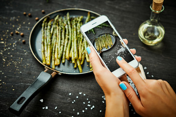 woman's hands are holding the phone and taking a picture of delicious young asparagus on a wooden table
