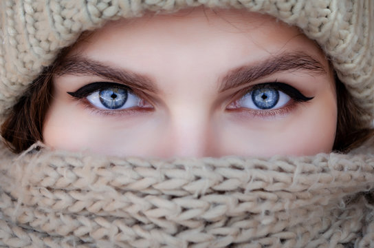 Close-up portrait of a woman in a scarf and hat with beautiful blue eyes