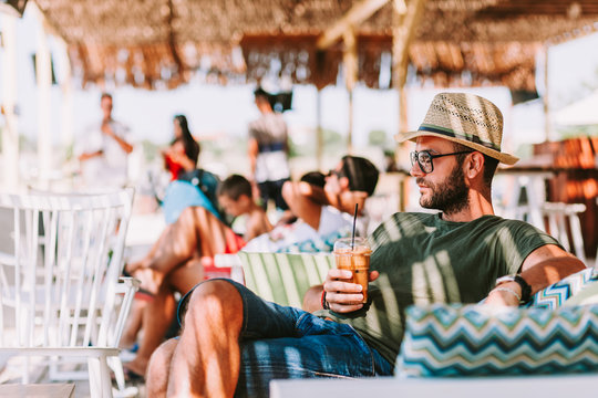 Young man drinking ice coffee in a beach bar