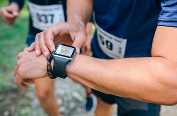 Unrecognizable sportsman looking at a smartwatch during a race