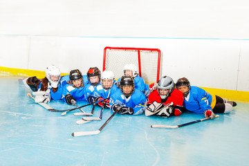 Happy boys and girls laying on ice hockey rink