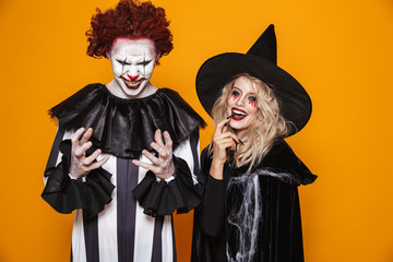 Image of witch woman and clown man wearing black costume and halloween makeup smiling at camera, isolated over yellow background