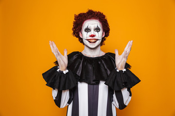 Young clown man 20s wearing black costume and halloween makeup looking at camera, isolated over yellow background