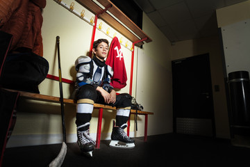 Boy sitting on the bench in hockey dressing room