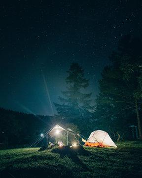 森の中でキャンプ 夜のテントとタープ