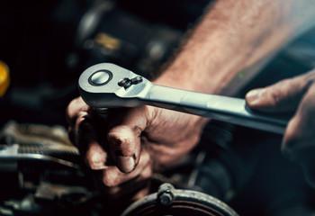 Fotobehang - Auto mechanic working on car engine in mechanics garage. Repair service. authentic close-up shot