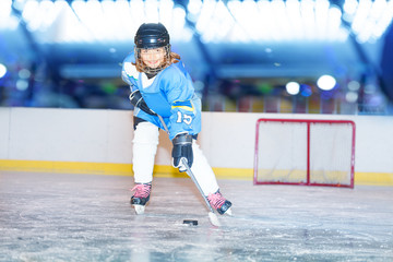 Happy girl passing the puck during hockey game
