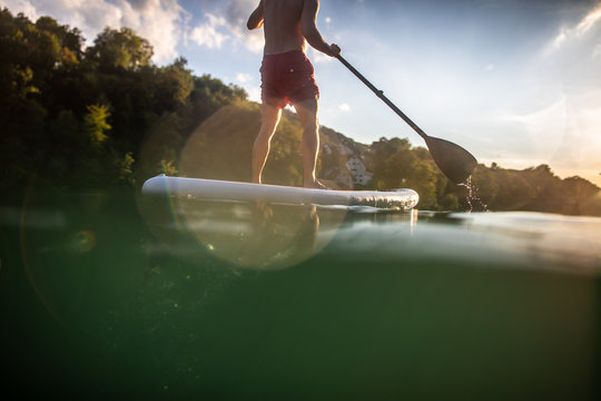 Handsome young man on a paddle board. Getting a great exercise on a lovely river in warm evening sunlight
