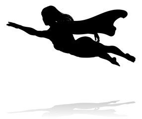 A woman caped superhero flying in silhouette