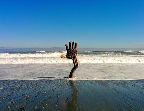Driftwood hand coming out of beach with waves and blue sky